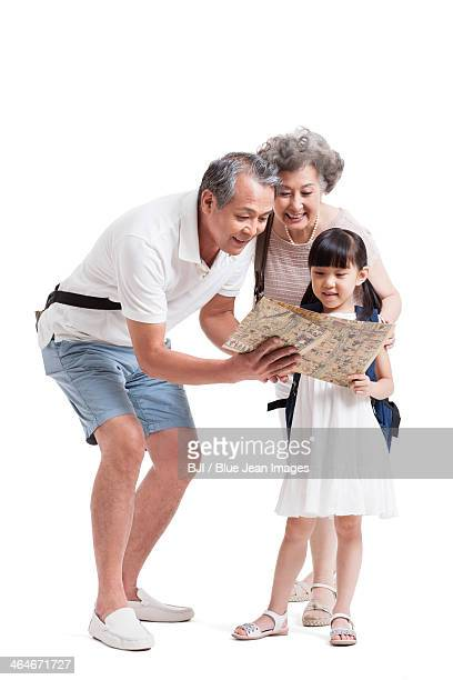 Happy grandparents and granddaughter with map