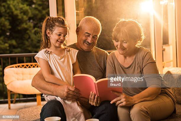 Happy grandparents reading a book to their granddaughter at home.