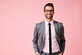 Happy grey suit guy in pink studio, portrait