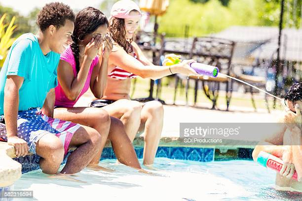 Happy group of college kids playing by the pool