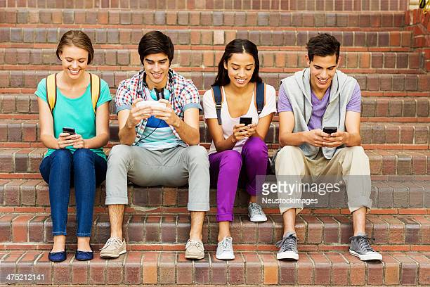 Happy Group Of College Students Texting On Steps
