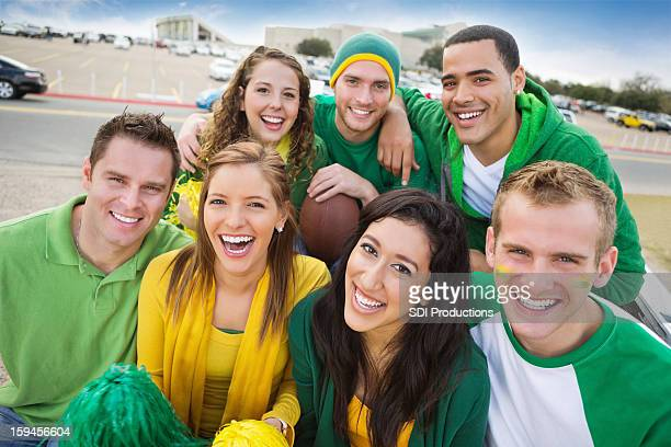 Happy group of fans tailgating at college football stadium