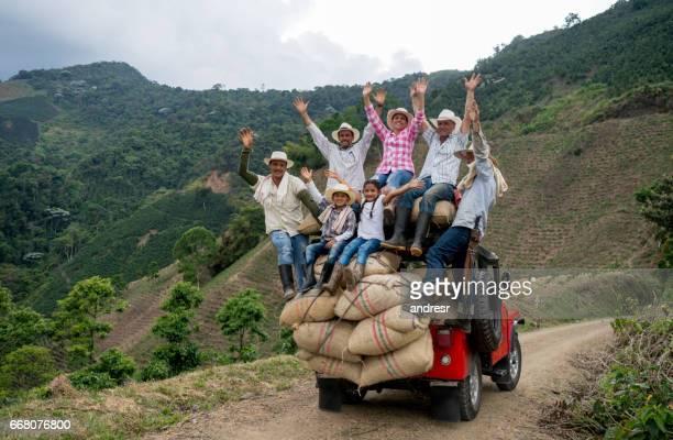 Gelukkig groep boeren koffie op een auto te vervoeren