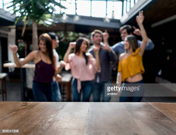 Happy group of friends dancing at a bar