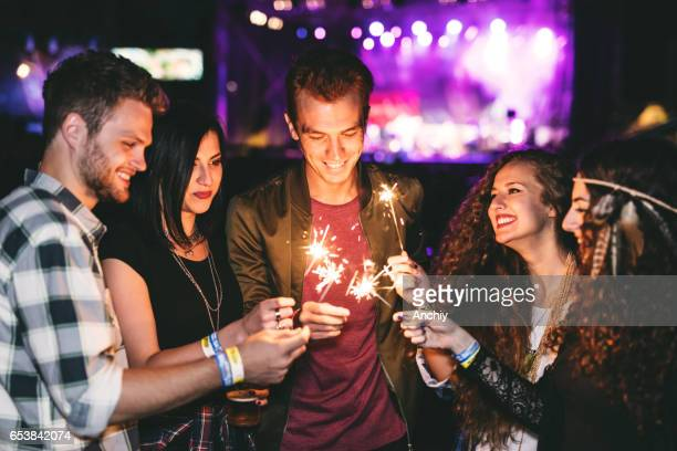 Happy group of friends holding sparklers in front of the concert stage