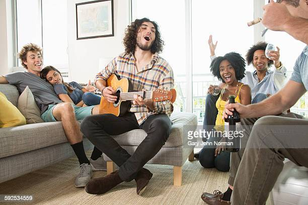 Happy group of friends singing and playing guitar.