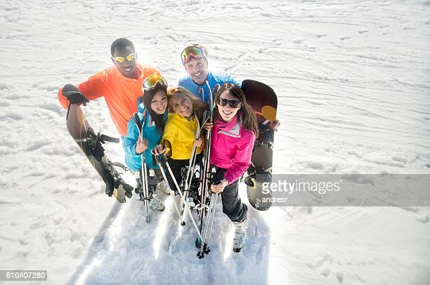 Happy group of friends skiing and snowboarding
