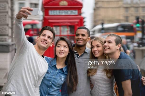 Happy group of friends taking a selfie in London