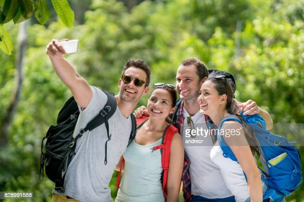 Happy group of hikers taking a selfie outdoors