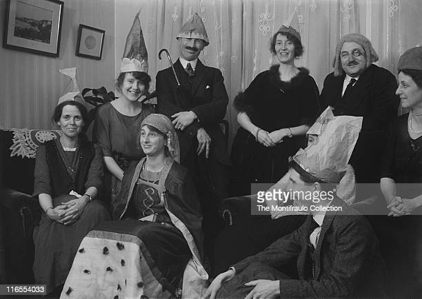 Happy group of people in costume wearing paper party hats judges wig fortune teller's head scarf together with a man pulling a funny face and holding...