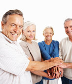 Smiling elderly men and women standing together with hands together on white