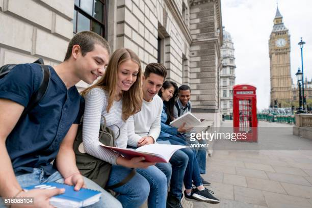 Happy group of students in London studying outdoors