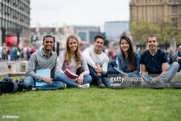 Happy group of students studying outdoors and looking at the camera