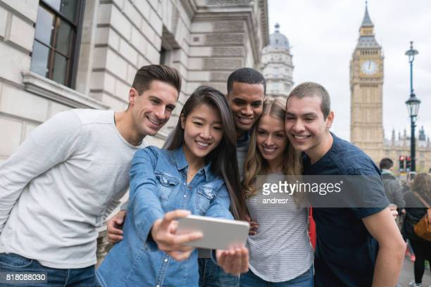 Happy group of tourists taking a selfie outdoors in London