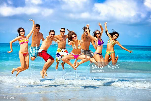 Happy group of young people jumping on a beach party