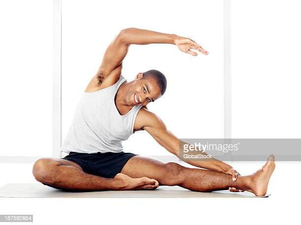 Happy guy doing stretching exercises on a yoga mat