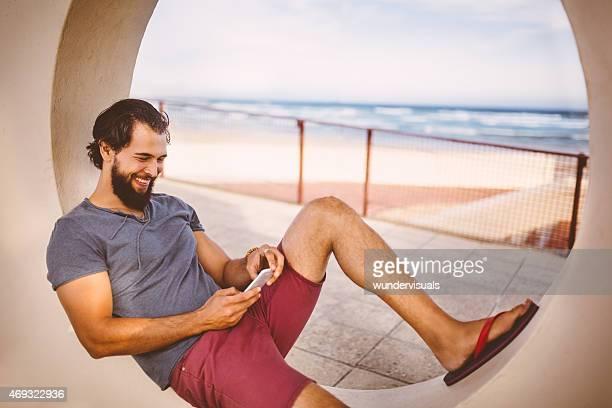 Glücklicher Mann auf seinem Handy am Strand