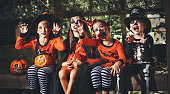 happy Halloween! a group of children in suits and with pumpkins in the forest