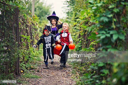 Happy halloween kids running on a path