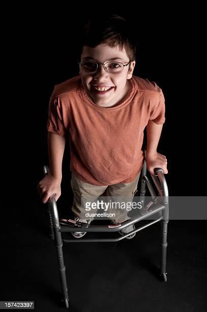Happy handicap boy standing in walker look up at viewer