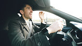 Happy handsome businessman driving car and singing. Man is happy after making deals and drive home