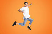 Full length photo of a smiling young man showing okay symbol and jumping isolated over yellow studio background. Happy handsome guy.