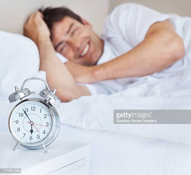 Felice bell'uomo con orologio sveglia in primo piano