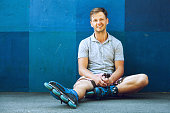 Portrait of happy handsome young roller in inline skates sitting against blue wall.