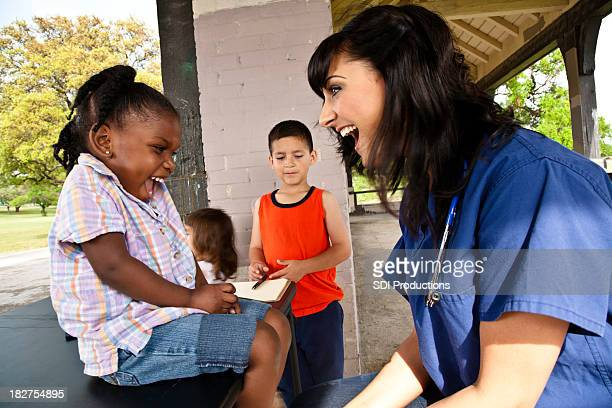 Happy Healthcare Professional Giving Health Exam to Children