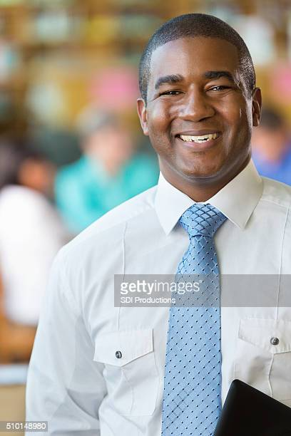 Happy high school teacher in school library