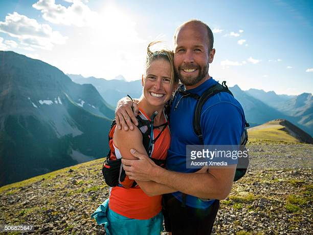 Happy hikers embrace on mountain summit