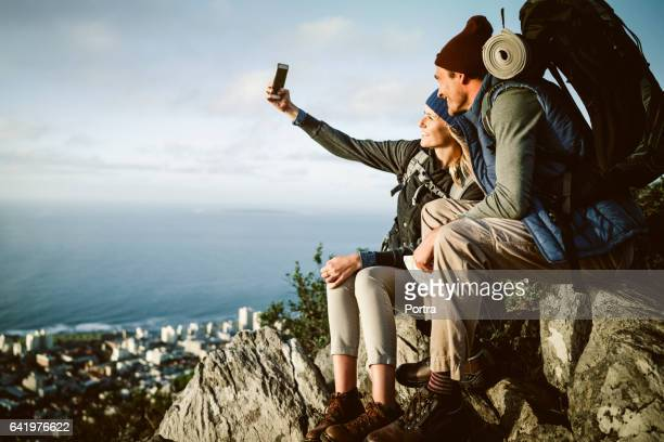 Happy hiking couple taking selfie on mountain