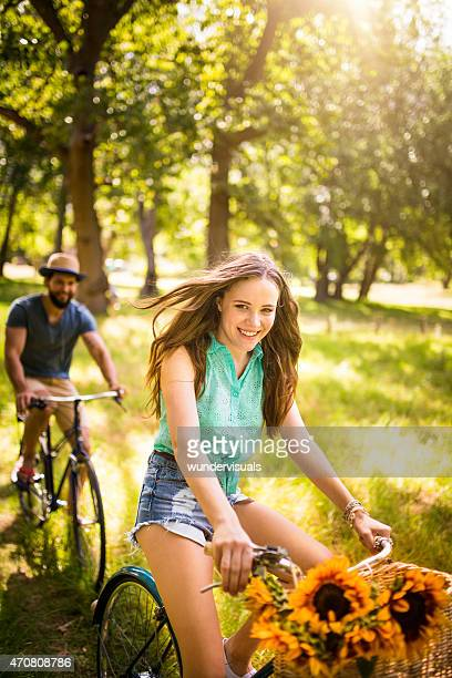 Happy Hipster couple cycling in park during summer