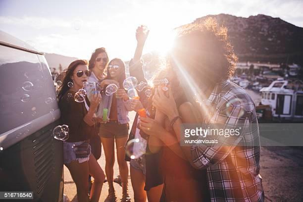Glücklich hipster Freunde feiern mit Blasen vor ein Sonnenuntergang