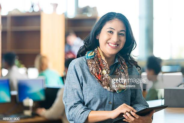 Happy Hispanic adult woman using digital tablet in college library