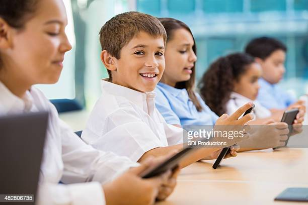 Happy Hispanic boy using technology in private school classroom