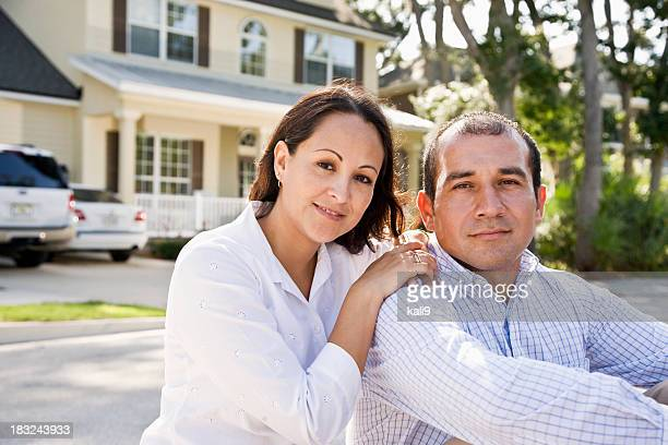 Happy Hispanic couple sitting with house in background