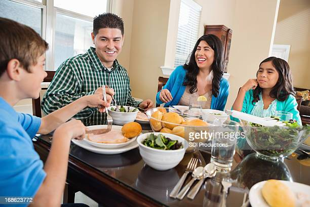 Happy Hispanic family enjoying dinner together in dining room