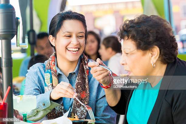 Happy Hispanic woman having lunch with grandmother at restaurant