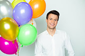 Happy holiday photo. Young handsome smiling man with a lot colored Balloons with helium in hand on the white background.