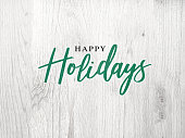 Festive Happy Holidays Calligraphy Text Over White Rustic Wood Background