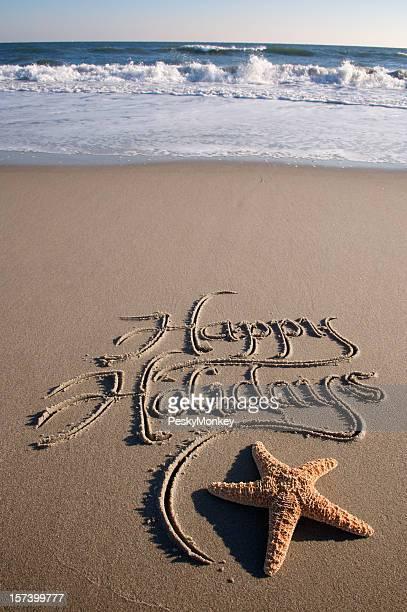 Happy Holidays Message Handwritten on Beach with Crashing Waves