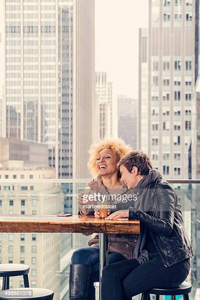 Happy hour for girlfriends on rooftop terrace in New York.