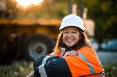 Senior woman engineer wearing protective wear in work - outdoor at sunset