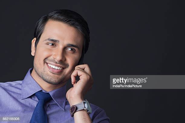 Happy Indian businessman using mobile phone over white background
