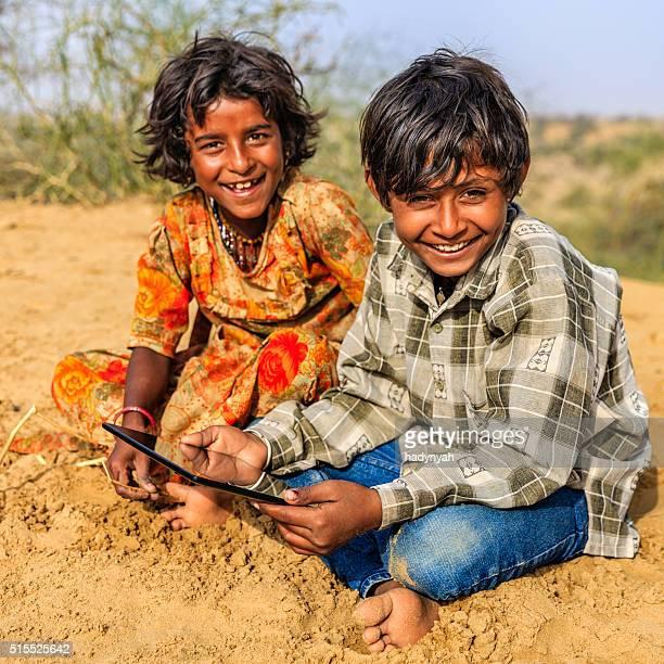 Happy Indian children using digital tablet, desert village, India