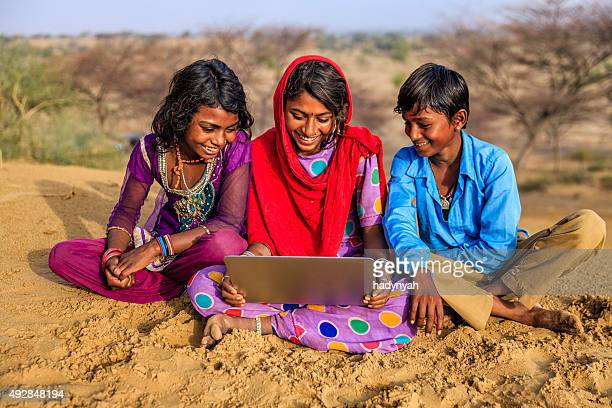 Happy Indian children using laptop, desert village, India