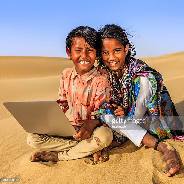 Happy Indian children using laptop, desert village, India