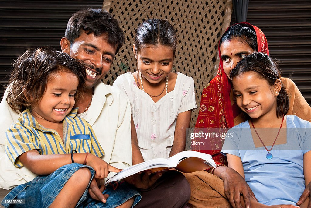 Happy Indian Family Sitting Together Reading A Book : Stock Photo