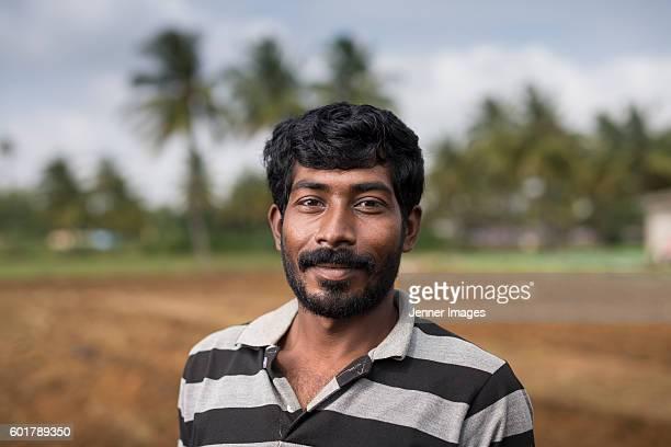 Happy Indian farmer standing in a field.